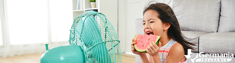 Young girl sitting in front of a fan, saving energy during the Texas summer