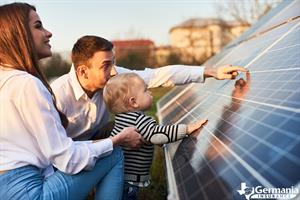 Parents showing their young child a solar panel array