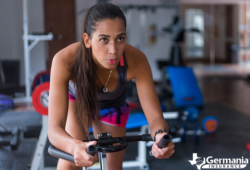 A woman riding an exercise bike after building a home gym