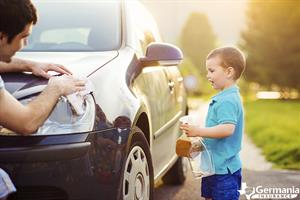 Father and son cleaning a car
