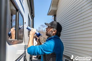 A man caulking windows, performing essential RV maintenance