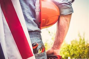 A man with a hard hat and American flag representing the history of Labor Day in the USA