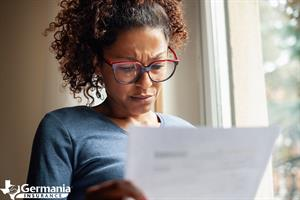 A concerned woman looking at a bill that might indicate deed theft scams