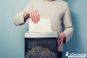 A man destroying sensitive documents with a shredder