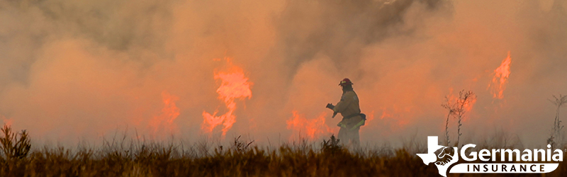 A firefighter standing in the grass in front of a Texas wildfire