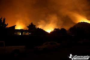 Silhouette of a house with a wildfire burning behind it