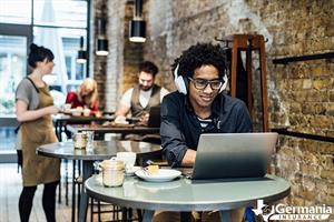A man in a coffee shop staying safe on public Wi-Fi