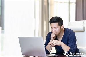 A man suspiciously looking at his computer