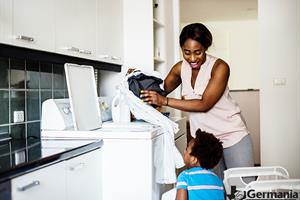 A mother and son using a dryer to do their laundry