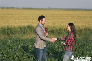 A Texas farmer shaking hands in a field with a farm and ranch insurance agent.