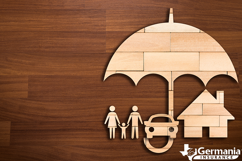 A wooden cutout depicting a family and their assets covered by umbrella insurance.