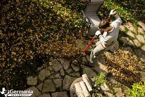 A man raking fall leaves as part of a fall home maintenance checklist